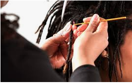 Lady using crochet method to fix black dreads.