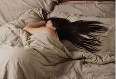Woman with long black hair sleeping on a bed with beige sheets.