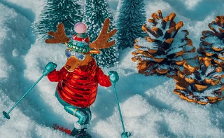 Moose in red and green snow gear skiing down a hill.