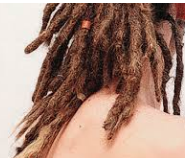 Shoulder length dark blond dreads with two hair clasps.